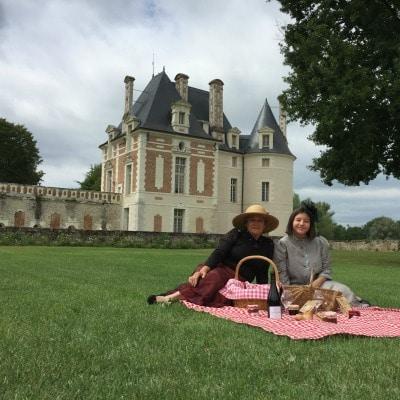 Sur fond de château de Selles sur Cher, deux dames 1900 pique-niquent sur une nappe vichy rouge