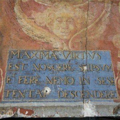 Citation latine peinte de couleur dorée sur fond bleu.